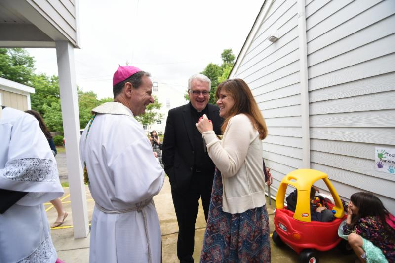 Kathleen Wilson shows Bishop Burbidge and Father Rooney the outdoor play area. (May 6, 2017)